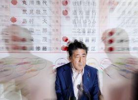 自民党本部の開票センターで、テレビ中継の選挙情勢を確認する安倍首相=21日午後10時56分、東京・永田町(ズーミングしながら撮影)