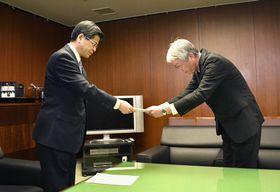 再発防止に関する勧告書をスバルの中村知美社長(右)に手渡す石井国交相=14日午後、国交省