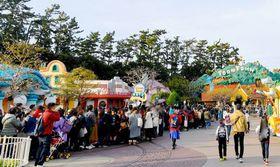 東京ディズニーランドの「ミッキーの家とミート・ミッキー」(右奥)に並ぶ来園者=18日午前、千葉県浦安市