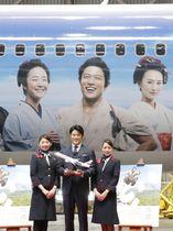 大河ドラマ「西郷どん」の出演者らがデザインされた日本航空の特別塗装機と、主人公の西郷吉之助を演じる鈴木亮平さん(中央)=21日、羽田空港
