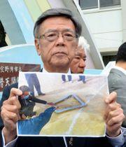 沖縄県宜野湾市の市立普天間第二小学校前で、落下した米軍ヘリの窓枠の写真を見せる翁長雄志知事=13日午後