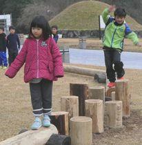 流木を活用した平均台の遊具の上を歩く子どもたち