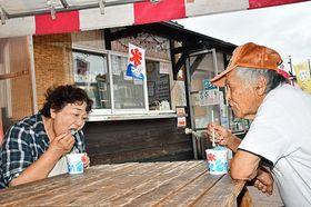 かき氷を食べて涼む観光客ら=23日午後2時半ごろ、平川市の道の駅いかりがせき