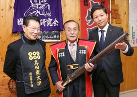 長野県上田市の山家神社の宝物庫で発見された、杉山弥一郎製造の火縄銃。左は鉄砲研究家の沢田平さん、右は同神社の押森慎宮司=12日午後、長野県庁