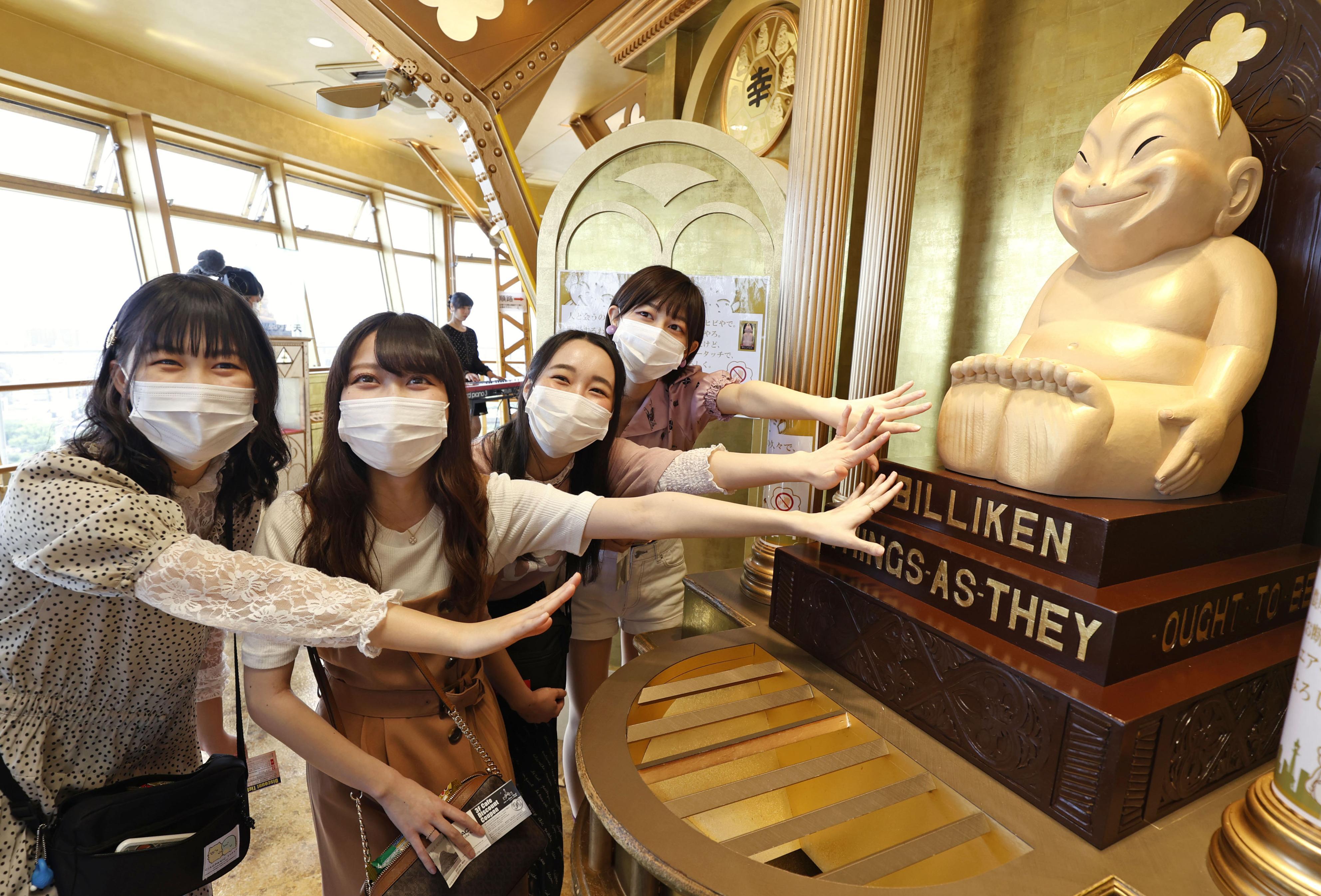 営業が再開された「通天閣」展望台でビリケンさんにエアタッチし笑顔の女性たち=30日午前、大阪市