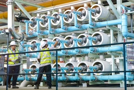 再生水プラントで逆浸透膜装置を点検するエンジニア。プラントは24時間体制で稼働し「ニューウオーター」を供給している=3月、シンガポール(共同)