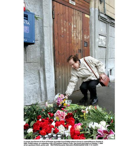 モスクワ中心部で、殺害されたアンナ・ポリトコフスカヤさん宅前に花を手向ける女性(ロイター=共同)