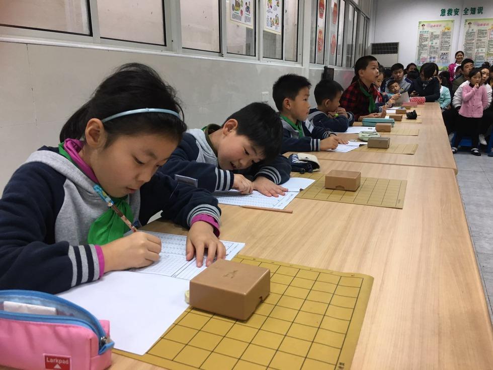 詰め将棋を将棋ノートに書き写す上海の子どもたち