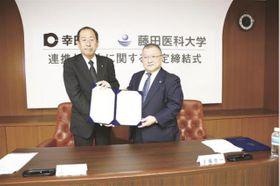 協定を締結した才藤学長(右)と成瀬敦町長
