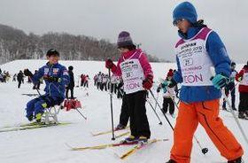 チェアスキーの選手(左)と一緒に滑る子どもたち=16日、札幌市豊平区(小川正成撮影)
