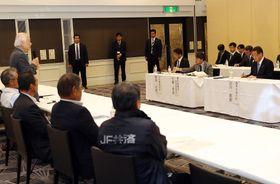 馬奈木弁護団長の訴えをメモに取る吉川農相(右)=佐賀市、ザ・ゼニス