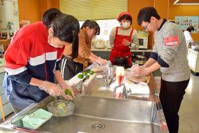 乾パンなどを使って調理する参加者