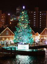 「はこだてクリスマスファンタジー」が始まり、観光名所赤レンガ倉庫前の海上で明かりがともった巨大ツリー=1日夜、北海道函館市