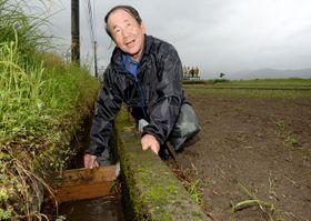 作付けに備えて水路の取水口を確認する原田さん。「一日も早い全面再開を」と願う=18日午後、えびの市向江