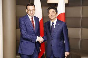 会談前に握手するポーランドのモラウィエツキ首相(左)と安倍首相=24日、ブラチスラバ(共同)