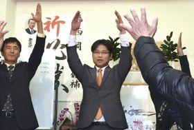 山口県美祢市長選で再選を果たし、支援者らと万歳する西岡晃氏(中央)=10日夜