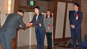 田中会長(左)から記念品を受け取る受賞者