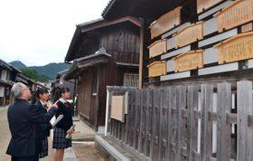 【生徒らを連れて観光地「関宿」を案内する本間事務局長(左手前)=亀山市関町で】