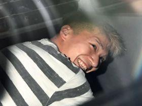 事件翌日、送検のため神奈川県警津久井署を出る車の中で笑みを浮かべた植松聖被告=2016年7月27日午前、相模原市緑区