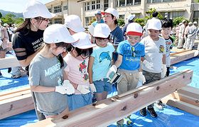 選手村の建材に上手に刻印する子どもたち=山形市・西山形小