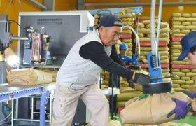 2015年10月、コメの全量全袋検査で、玄米の袋を運ぶ検査員=福島県二本松市