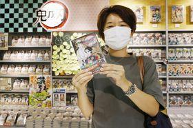 漫画「鬼滅の刃」の最新刊21巻を購入する女性=7月3日、東京都渋谷区の「SHIBUYA TSUTAYA」