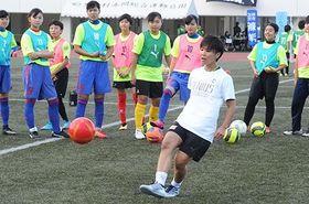 サッカークリニックでコースを狙うシュートを打つ高良亮子さん=12日、恩納村の赤間陸上競技場