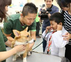 白衣を着て獣医師気分を味わう子ども=高松市東植田町、さぬき動物愛護センター