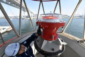 80年余り横浜航路を見守ってきた横浜外防波堤北灯台。廃止となりLED灯器を撤去する海上保安官=横浜港