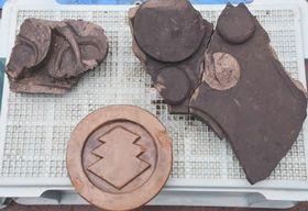 小倉城の堀から見つかった瓦。細川家の家紋「九曜」(右)、小笠原家の家紋「三階菱」(下)、豊臣家の家紋「桐」(左)が入っている