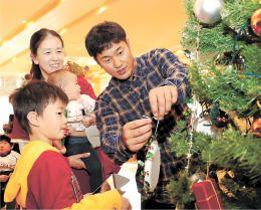 子どもたちと一緒にクリスマスツリーに飾り付けをする銀次選手