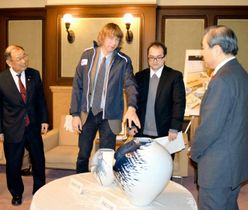 いよかん大使と砥部焼大使を委嘱されたトム・ケンプ氏(左から2人目)と作品=28日午後、県庁