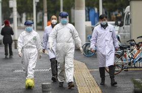 防護服を着て中国・武漢市内を歩く医療従事者=26日(AP=共同)