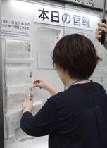 政令恩赦「復権令」と特別基準恩赦が掲載された官報を掲示する国立印刷局の職員=22日午前8時30分、東京都港区