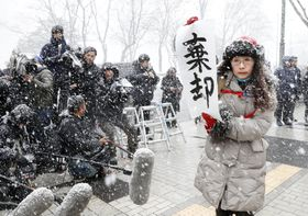 北海道恵庭市の女性会社員殺害事件の第2次再審請求審で、棄却と書かれた紙を掲げる関係者=20日午後、札幌地裁前