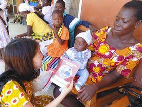 ガーナで母親たちに母子手帳の試行版の感想を尋ねるJICAの専門家(左)=JICA国際協力専門員の萩原明子さん提供