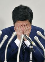 記者会見を終え、両手で顔を覆う男性。東京・池袋の暴走事故で妻の松永真菜さんと長女莉子ちゃんを亡くした=12日午後、東京・霞が関の司法記者クラブ