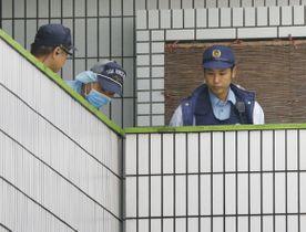 死亡している女性が見つかったアパートを調べる捜査員ら=15日午後4時37分、沖縄県宜野湾市