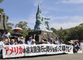 長崎市の平和公園で、米国の臨界前核実験に抗議し座り込みをする被爆者ら=12日午後