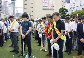 福岡市役所前の広場で開かれた飲酒運転撲滅大会で黙とうする市民ら=25日午後