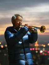 朝焼けを背に、最後となるトランペットを奏でる松平晃さん=17日午前6時37分、神戸市中央区神戸港地方、ビーナスブリッジ(撮影・吉田敦史)
