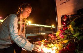 17日、ウクライナ南部クリミア半島のシンフェロポリで、ケルチで起きた銃乱射事件の犠牲者を追悼し、ろうそくをともす女性(タス=共同)