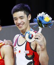 体操の世界選手権男子個人総合で獲得した銅メダルを手に笑顔の白井健三=5日、モントリオール(共同)