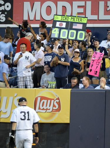 守備に就くヤンキースのイチローに「4000」と表示した「イチ・メーター」を掲げ祝福するエイミー・フランツさん=8月22日、ヤンキースタジアム