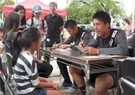 参加者らの似顔絵を描くロアッソの選手ら=熊本市東区
