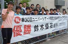 母校の後輩と笑顔を見せる鈴木(左)。陸上グラウンド脇にはユニバ優勝を祝う横断幕が掲げられている