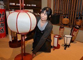 丸みがある形が特徴の「あこだあんどん」(手前左)など、出展する収蔵品を見る宮坂さん