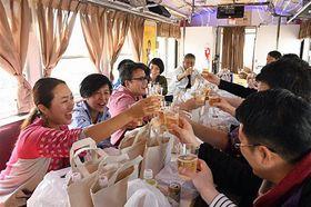 「ハイボール列車」発車直後に乾杯する参加者たち=21日、午後2時すぎ