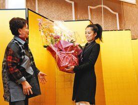 パーティー会場で参加者から花束を受け取る松葉さん(右)=松阪市の華王殿で