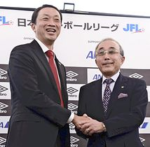 JFL昇格が決まり握手する大倉社長(左)と桑原理事長=都内